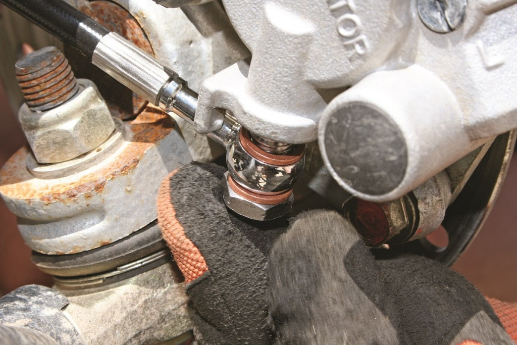 STEP 7: Route the lines to the caliper, make sure to clear any moving parts and won't get snagged by objects on the trail. With the lines routed to the brake calipers you can now install them using the supplied banjo bolts and crush washers like you did to the reservoir.