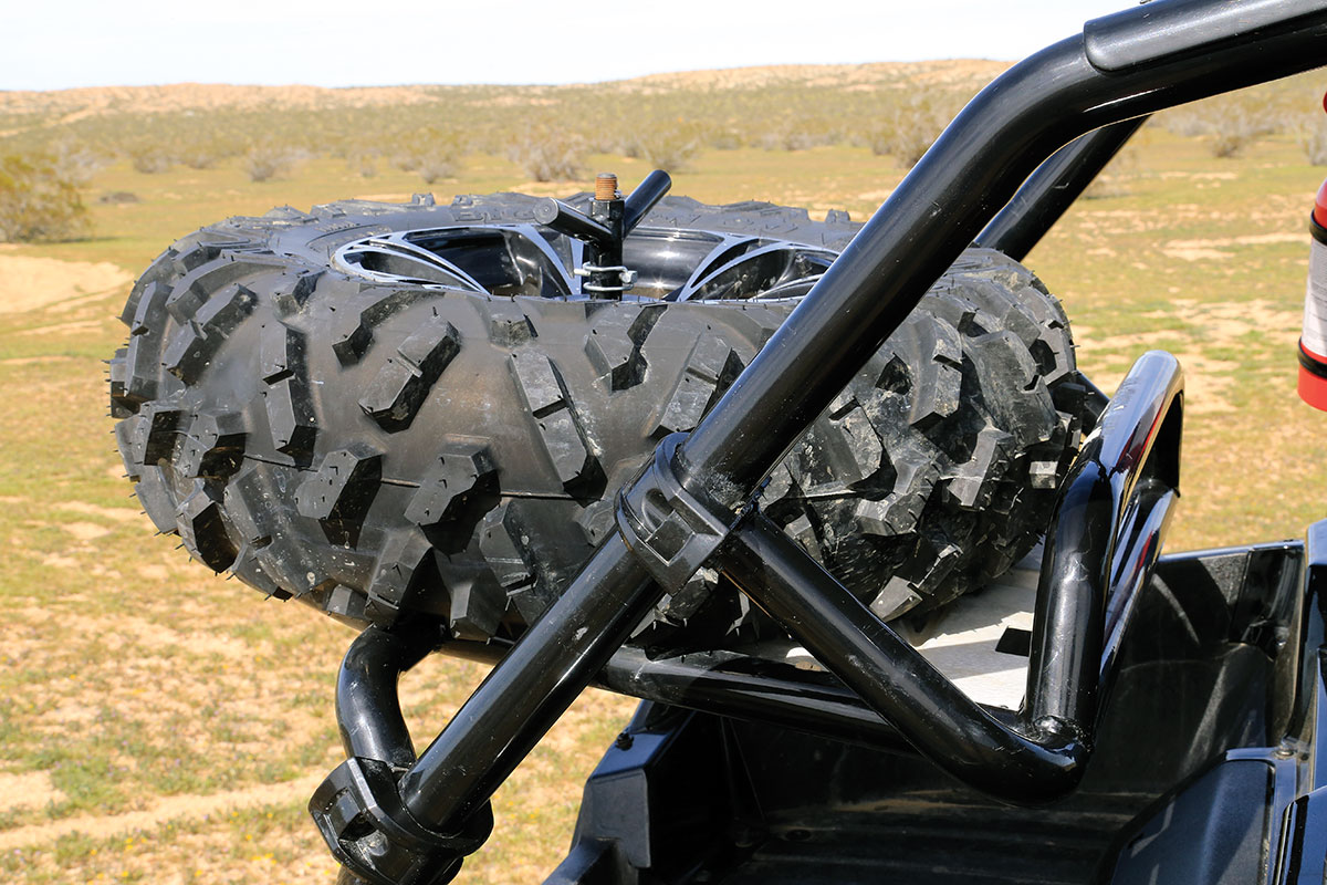 We received this machine with a factory spare tire carrier installed from Arctic Cat. The spare tire carrier slides on the downtubes for adjustment.