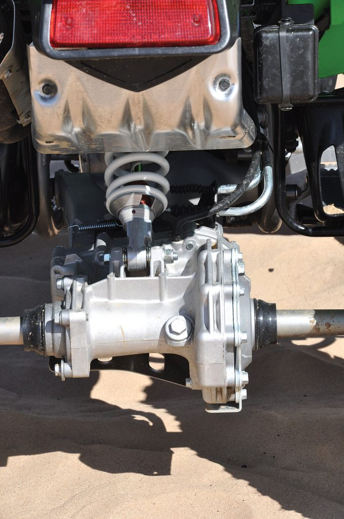 """The single-shock swingarm suspension on the Kawie 700 offers up considerably less travel at 7.9 inches than the Honda. Note the cable actuated rear """"wet"""" rear disc brake that resides in the rear axle pumpkin."""
