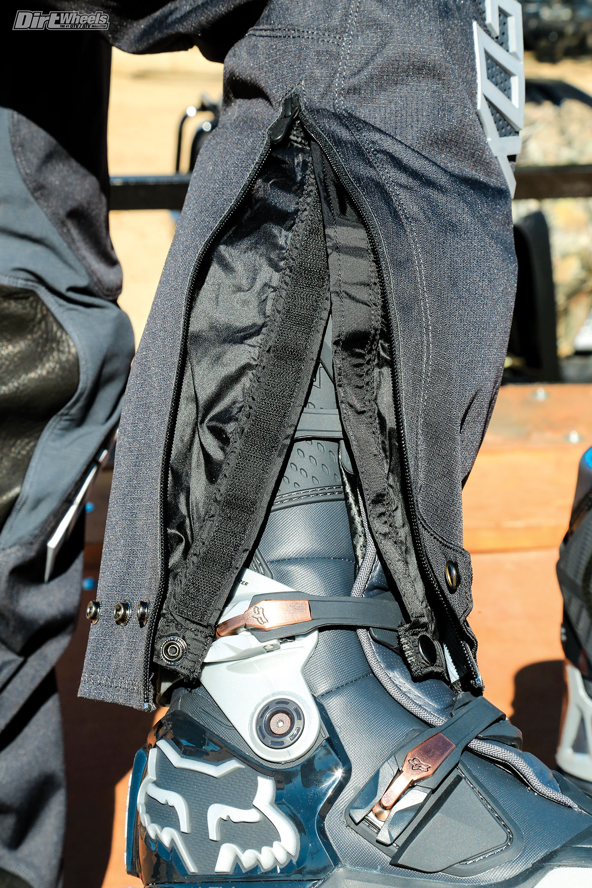 The EX pant requires you to unzip and open up the inner and outer panels to put the pant legs over the boots. There is a tab on the bottom of the inner leg panel that you can clasp to the boots so the pant doesn't ride up.