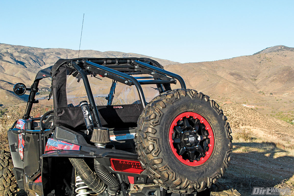 STI has great wheels and tires in their arsenal. The HD5 beadlock wheel has multiple color beadlock ring options to purchase them with. The rear bumper/spare tire holder is perfect for trail use. You can still access the bed of the RZR while having the ability to store more items on top of the cage extender. Tusk's quality rear window is best suited for machines with a full front window. Without a windshield, air funnels down your neck: not comfortable in the cold.